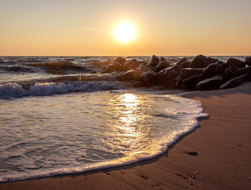 Sonnenaufgang am Fischlegerstrand in Damp - Die aufgehende Sonne spiegelt sich in den Wellen im Meer