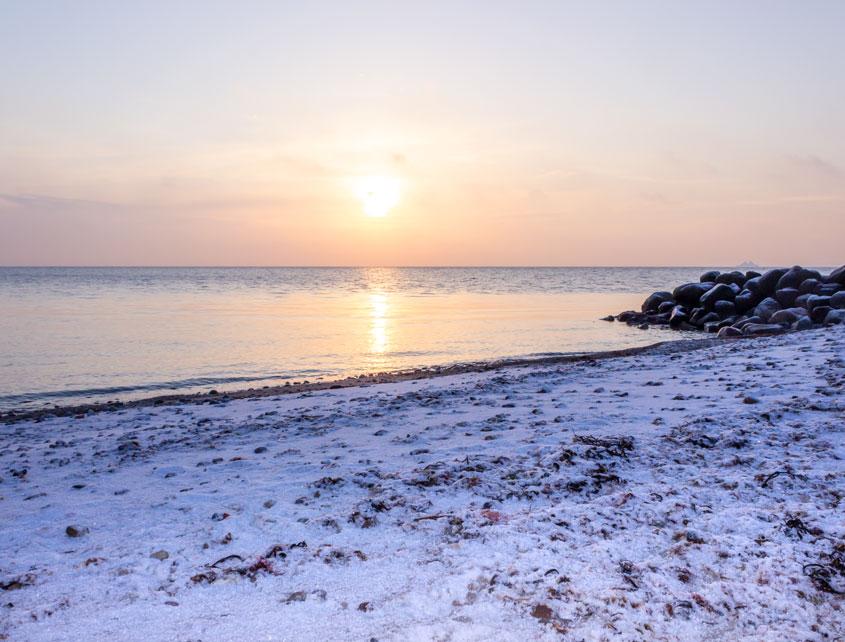 Sonnenaufgang am Strand in Damp im Winter - Am Strand liegt eine dünne Schicht Schnee