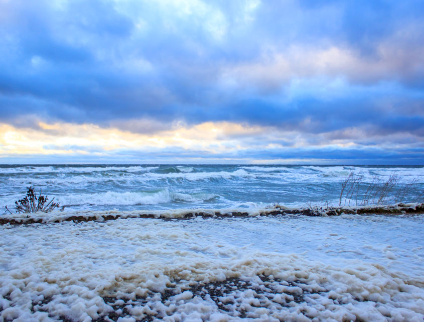 Wellen und Gischt am Strand in Booknis